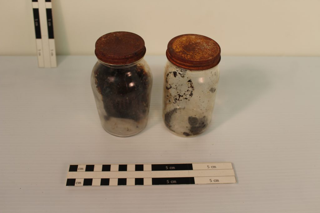 Glass jars from Calamity Camp. The left contains an unknown sludge, possibly food residue. The right is a plum preserve jar complete with possible plums. BLM Collection.