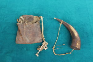 A very rare bag once used by a trapper to transport his belongings and a powder horn used to store gunpowder. MWC Collection.